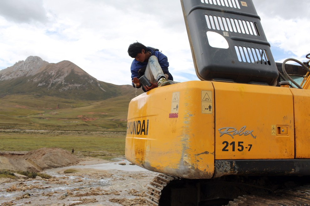 "A heavy-machinery operator takes a break. Construction in the region is increasing rapidly as the government implements its ""western development strategy,"" aimed at bringing prosperity to the region."