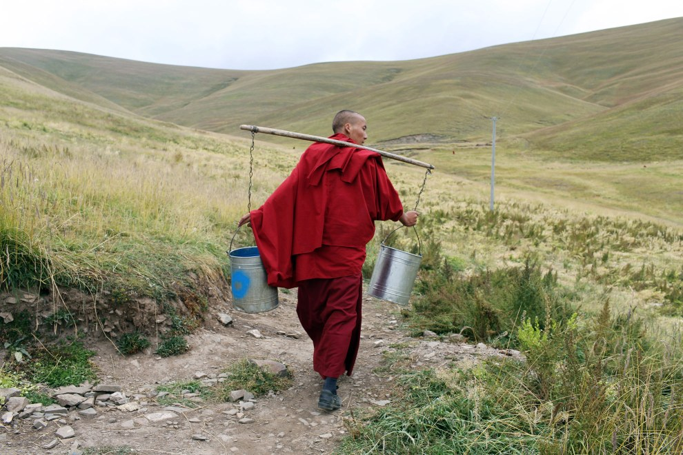 A Tibetan monk carries water cans toward a river on the grasslands. The water is for the local monastery in Sershul, in Sichuan Province on the Tibetan Plateau.