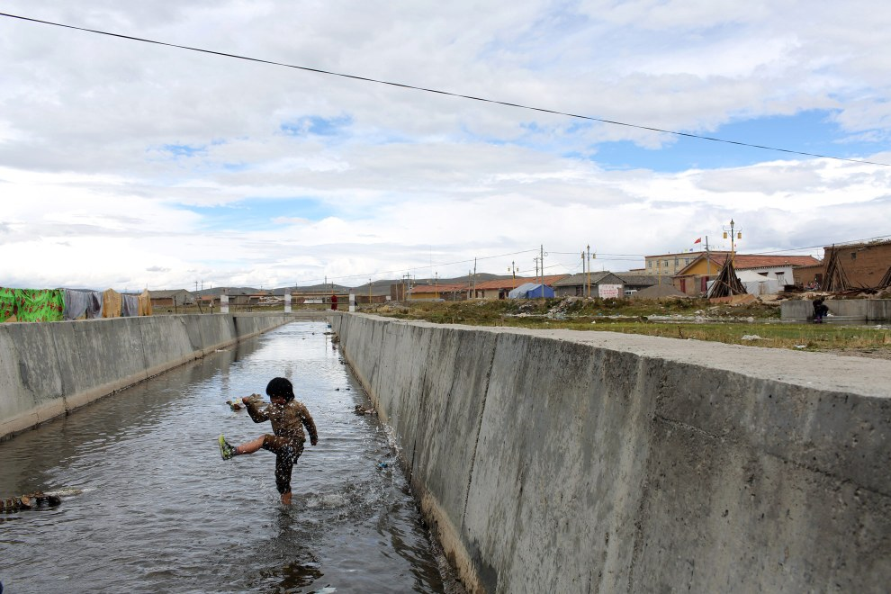 A young boy playing in an irrigation channel in the town of Sershul in Sichuan Province.