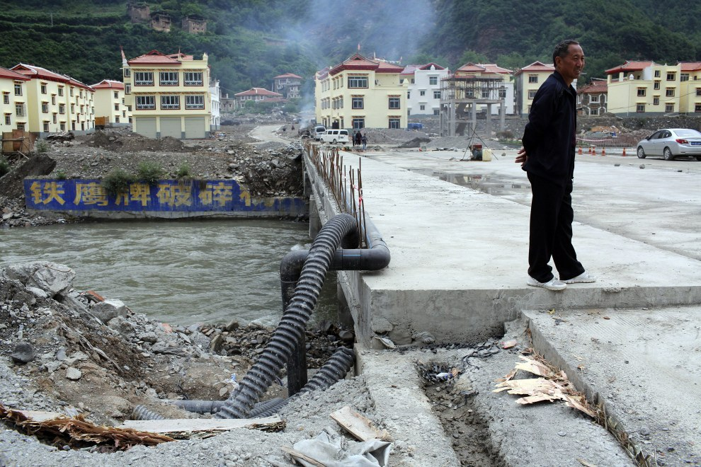 A man stands on a bridge that leads to newly built homes, built to rehouse local Tibetans displaced by the Maoergai Dam, in the Tibetan region of Aba.