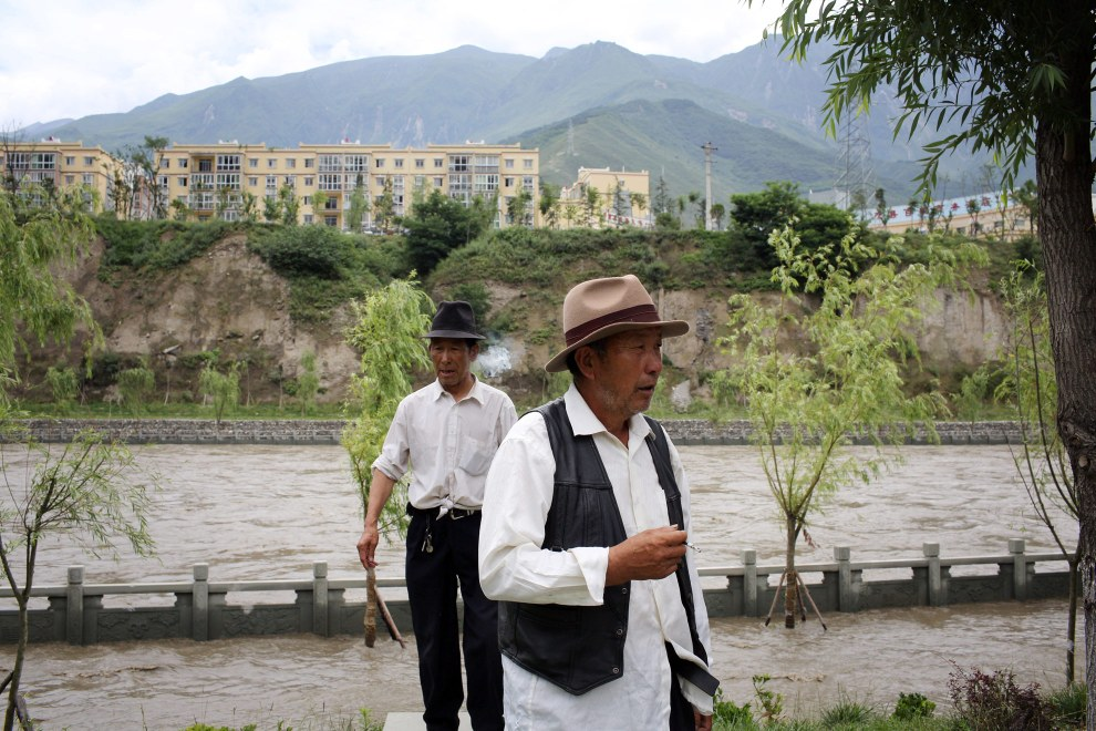 Two Tibetan men walking in front of a river that has breached its banks and flooded a nearby path. Flooding ravaged the region in 2012, causing the displacement of thousands of people.
