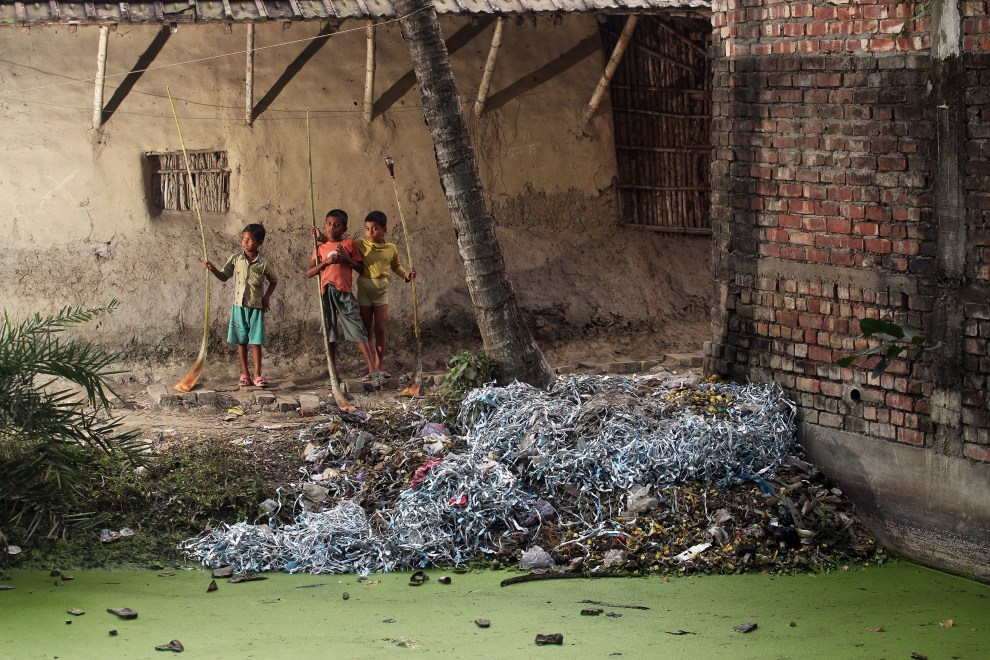Three boys stand near E-Waste discarded at the side of a small pond in the village of Sangrampur near Kolkata. As electronic waste is broken down, harmful elements such as mercury, lead and arsenic leach into the soil and water resulting in the long-term poisoning of local resources.