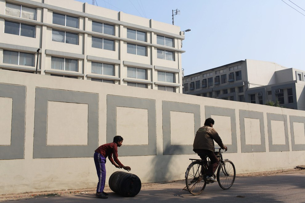 A child pushes a chemical barrel down the street, outside of a leather factory, in the Jajmau area of Kanpur.