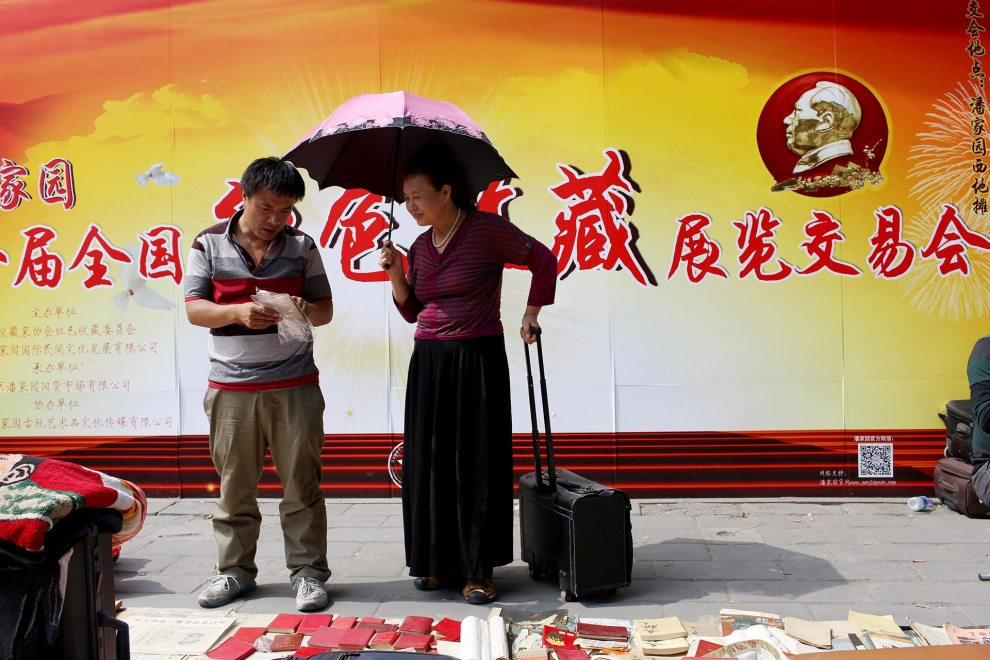 A seller with customer at a 'Red Memorabilia' sale, items associated with Mao Zedong, the Communist Party and the Cultural Revolution.