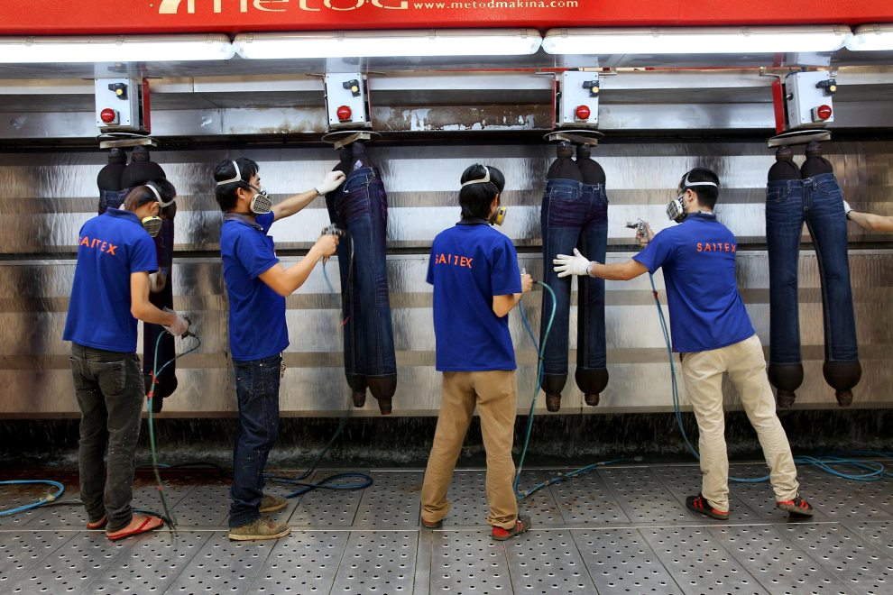 Workers apply coloured spray to jeans at denim detailing company, Sai-Tex, located outside of Ho Chi Minh City.
