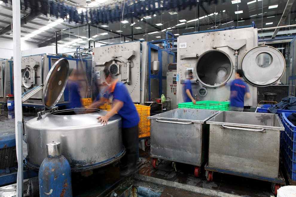 Workers operate large washing machines at denim detailing company, Sai-Tex, located outside of Ho Chi Minh City.