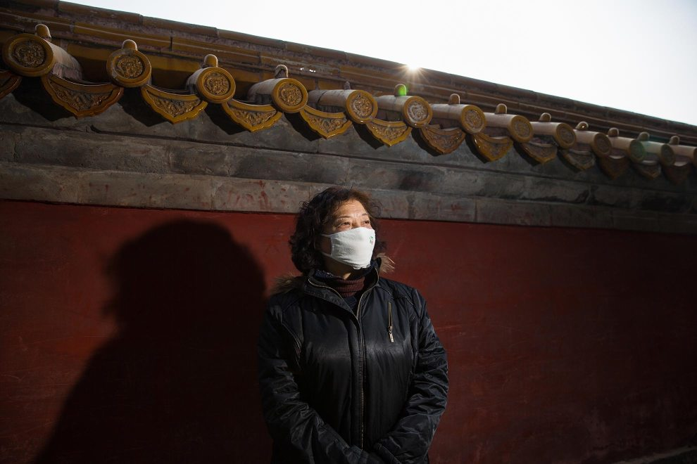 """Mrs. Zhang (62), a retiree in Beijing, stands near a wall in the capital's Ditan Park. """"Last year I bought a professional mask because I had a bad throat. The pollution made it worse. I think they are a bit strange looking. These past two years I've been wearing them. During the polluted days I definitely wear them. During the spring festival the pollution was really bad. I'm really scared of the pollution."""" PM2.5 reading - 365 - Hazardous"""