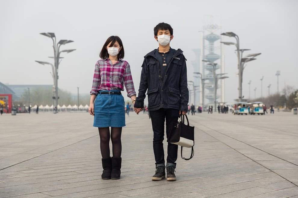 """A young couple, Ms. Lu and Mr. Li, hold hands during a walk through Beijing's Olympic Park. """"I'm pretty sad about this. It's worse and worse"""", explains Li. """"I think the pollution is bad for our health. The PM2.5 damages our lungs [but] we don't have any choice"""", he laments. """"I left China two and half years ago. Then it wasn't so bad. I've been abroad. I know what's good [air] and what's bad. Young people care more than old people. We have more information. We know how bad it is."""" PM2.5 reading - 218 - Very Unhealthy"""