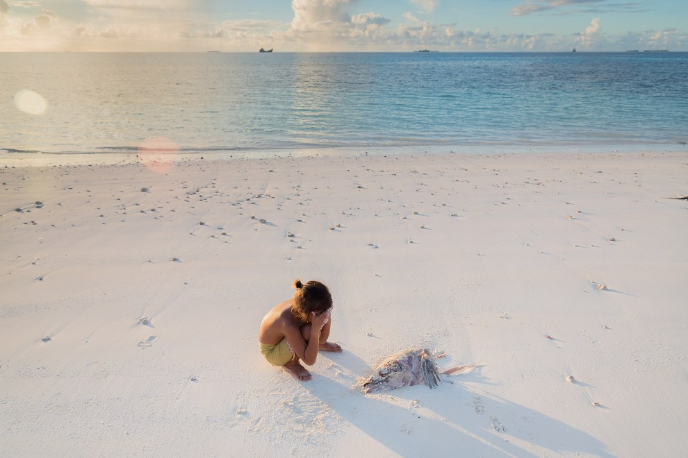 A young boy puts his hands over his face near a dead fish on the shores of a beach in Funafuti.