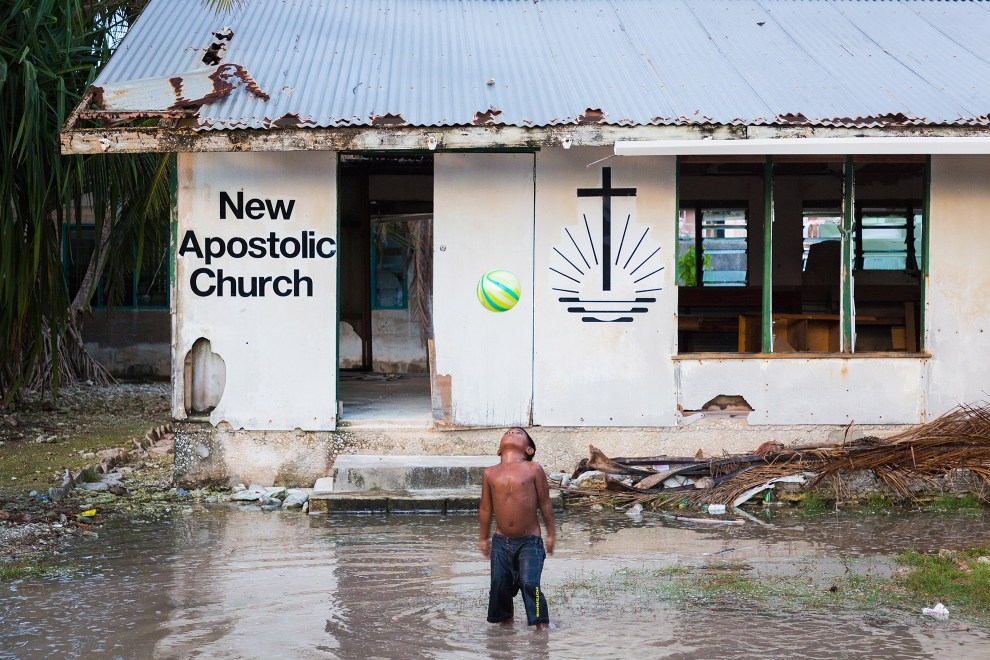 A young boy plays outside a dilapidated church that is being flooded during the spring King Tides.