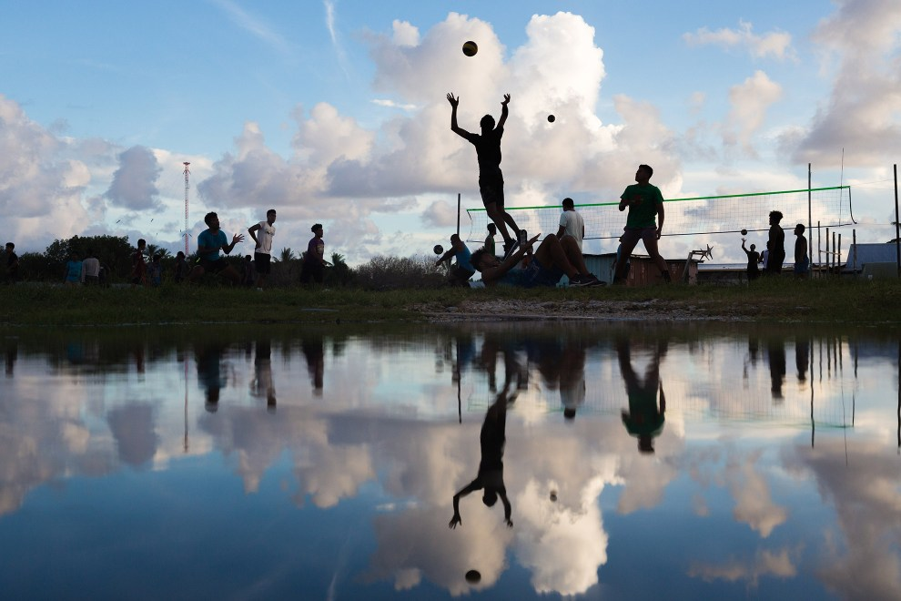 People play volleyball next to a flooded area near the airport runway, in downtown Funafuti.