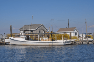 Deadrise fishing boat with crab shacks in the background.