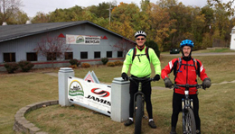 Mark Lang and Leslie Cook riding fat bikes in front of Hometown Bicycles Bicycle Adventure Center