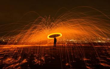 Photo at night of a person holding an umbrella or fire with fire sparks works flying around.