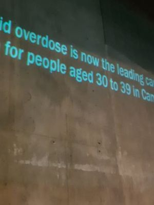 "Wall that has text projected on it: ""opioid overdose is now the leading cause of death for people aged 30 to 39 in Canada"" and # CantWait"