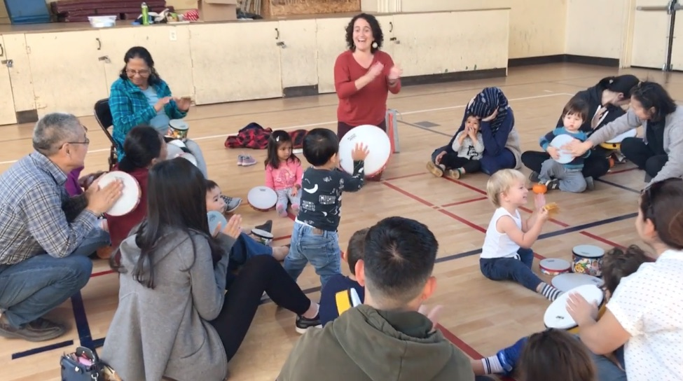 Kids, parents, and grandparents from China, Japan, US, India, Taiwan, and Pakistan drum zestily to a song celebrating the Diwali holiday