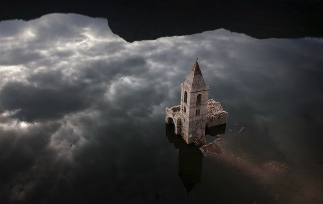 A church and the remains of an ancient village rise above the surface of the Sau reservoir in Vilanova de Sau, Spain.