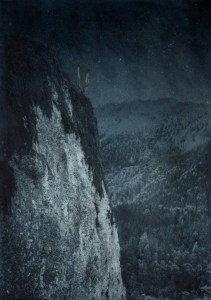 """Mystery surrounds a lonely outcropping in ski country. Approx. 28"""" x 20"""" handcrafted alternative process print (antracotypia (resinotype) on white plastic board; natural indigo pigment; wood frame, no glass). Edition #1/10. Signed original print offered by GALLERY5X7 at $1,000."""