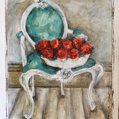 white bucket with red flowers on top of old white chair with blue upholstery