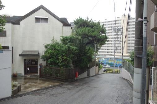 内田さん。昔海だった地にマンションが建つ風景を撮影。雨に濡れた坂の先に、目立つ青いトラックを収めるなど、よく練られた写真です。