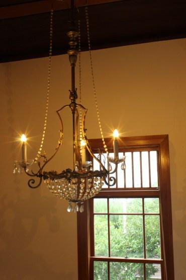 安西さん。光をテーマに撮影された一枚。シャンデリアの蝋燭の灯りが、窓の外の植物の緑と響き合って、よく映えています。