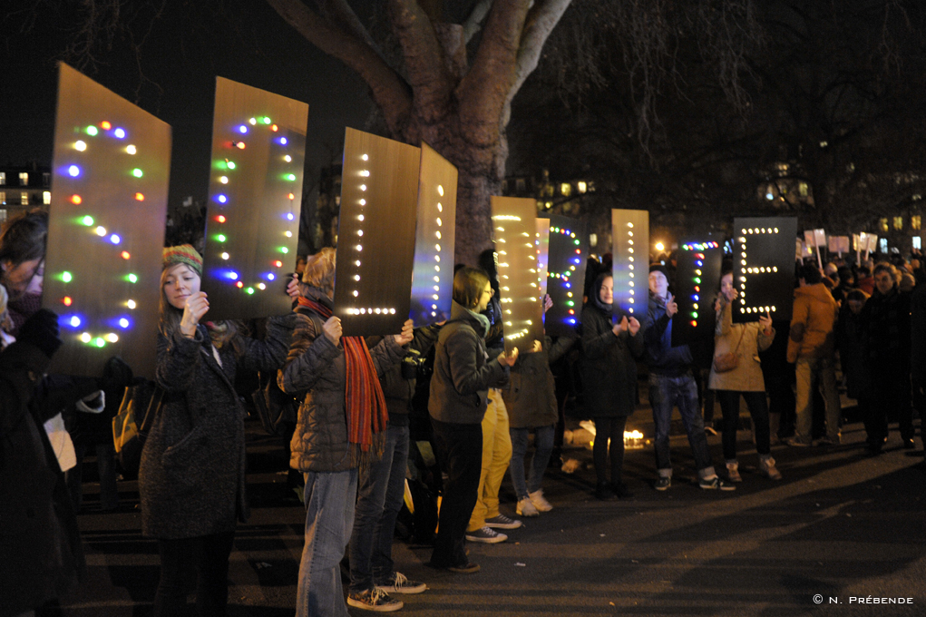 protestors holding up lighted letters on boards