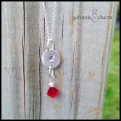 "LETTER DROP - Silver initial disc with wire wrapped birthstone drop. Shown with garnet (January). 18"" extra-fine silver-plated cable chain."