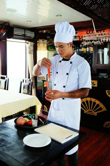 Der Koch schnitzt Dekoration aus einer Tomate