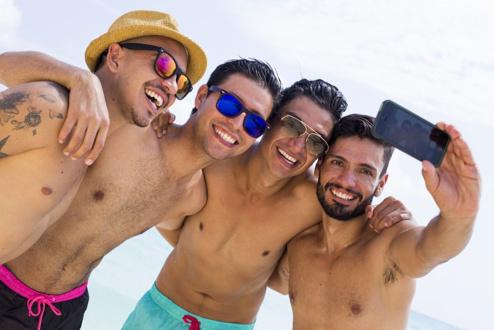 Group of young men having fun on a beach and taking a selfie.