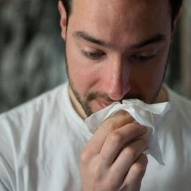 A man lifting a tissue to his nose.