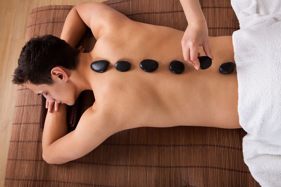 A man getting a hot stone message is enjoying the benefits of massage therapy.