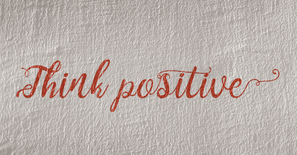 """calligraphy reading """"think positive"""" on textured paper"""