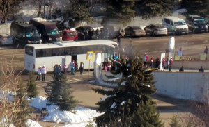 Long range shot from  gondola of IOC Evaluation Commission exiting bus for Medeu speed skating oval in Almaty,