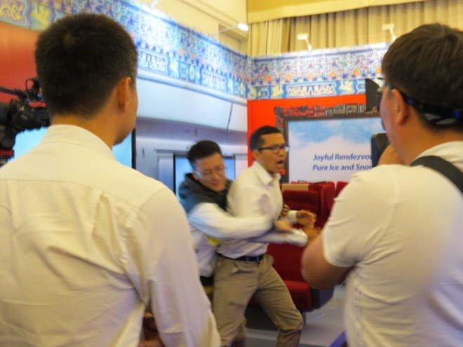 Tibetan protester tackled in Beijing 2022 exhibition room in Lausanne Palace Hotel (GamesBids Photo)