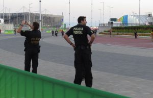 Federal Policemen stand watch at Rio 2016 Olympic Park, one snaps a souvenir shot (GamesBids Photo)