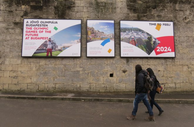 Passers by read an Olympic bid poster at the Citadella in Budapest Hungary February 20, 2017 (GamesBids Photo)