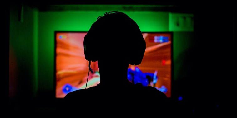 pc game player with headset in silhouette backlit by green wall and red glow from great gaming computer