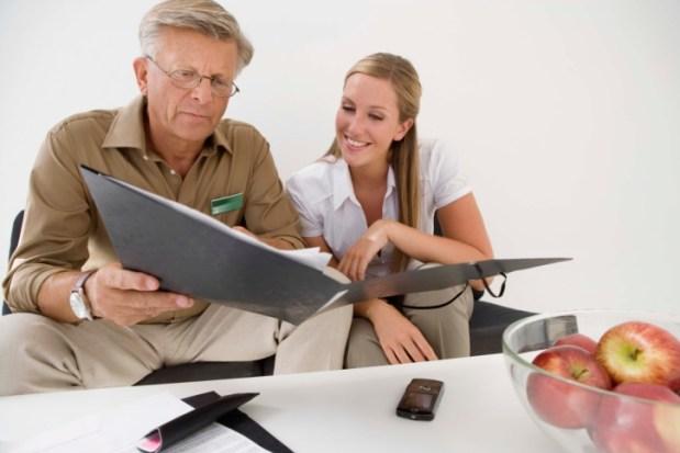 Un hombre mayor revisando una carpeta con papeles al lado de una mujer joven sentados en un sofa