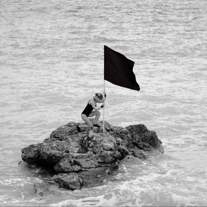 woman on rock formation holding a flag