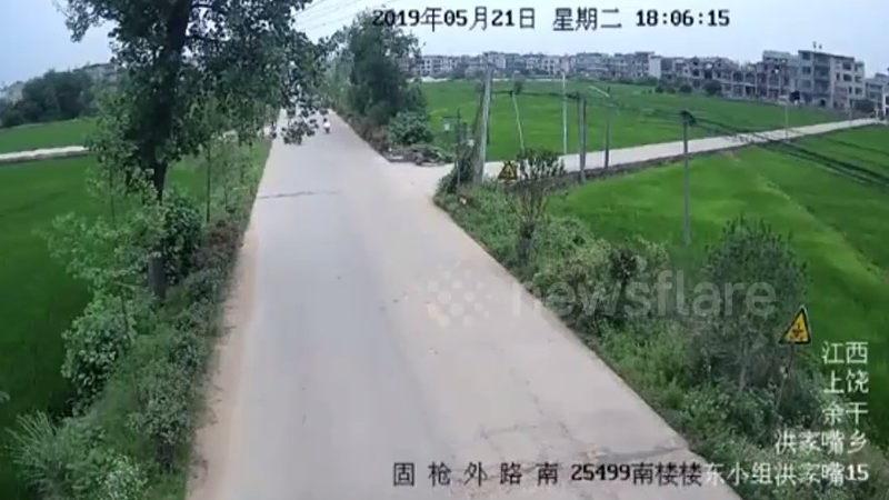 中国の郊外で起きたバイクと乗用車の正面衝突が瞬間。