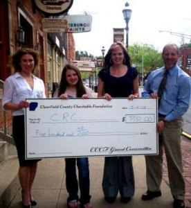 Rex L. Lettie, Clearfield County Charitable Foundation board member, right, presents a $500 check to Keely Casteel, president of the CRC, left, and Kellie Swales, second from right, Main Street Manager to help fund the CRC's 2013 Fall Festival. Also pictured is Gretchen Yeager, second from left, a student who helped prepare the grant application. (Provided photo)