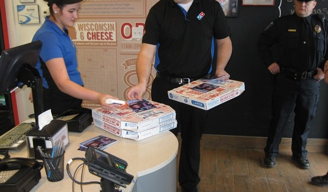 Domino's employees Kendra Beck and Greg Lightner are shown attaching the flyer to the pizza boxes. (Provided photo)