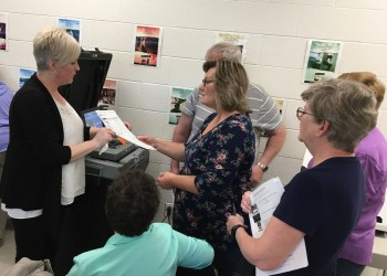 Centre County Election Coordinator Jodi Nedd, left, demonstrates how to scan a hand-marked paper ballot. (Provided photo)