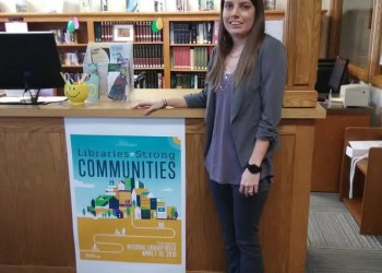 """Kayla Clark is the new Clearfield County Public Library Director. Here she poses at the desk of the Curwensville Public Library where a poster promotes National Library Week with its slogan """"Libraries=strong communities."""" (Photo by Julie Rae Rickard)"""