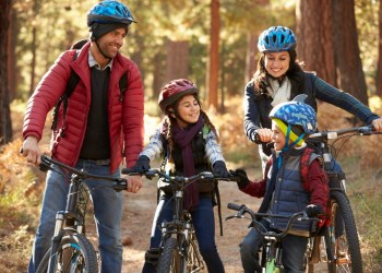 Hispanic family on bikes in a forest looking at each other