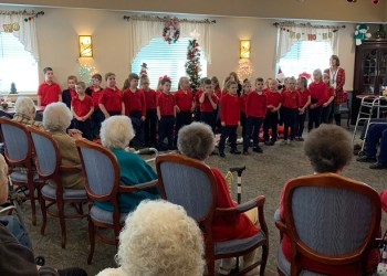 DuBois Central Catholic first graders brought gift bags of personal care items to residents in the Christ the King Manor Personal Care Unit.  Together, the residents and students enjoyed singing Christmas carols. (Provided photo)