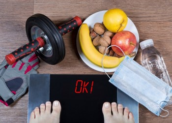 Girl checks her weight after quarantine. Digital scales with word ok surrounded by sport accessories, healthy food, water bottle and face mask. Concept of healthy lifestyle during self-isolation.