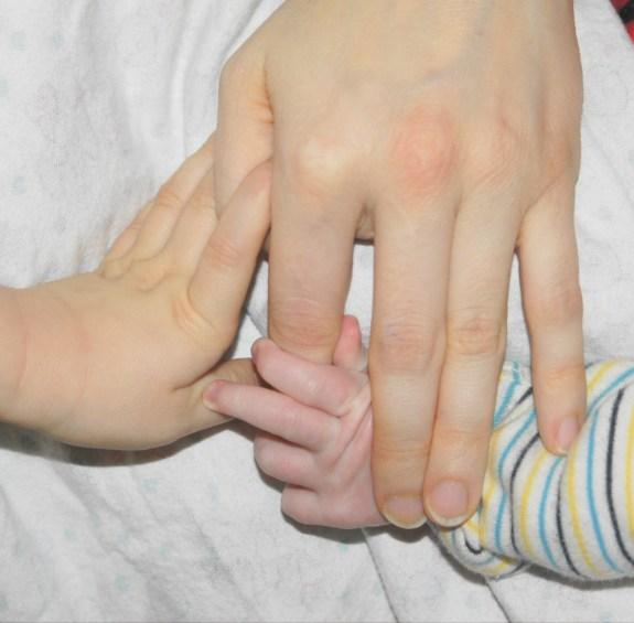 Babyhände, zwei Kindern gerecht werden