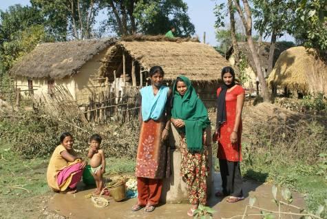 Frauen in Nepal holen Wasser aus einem Brunnen. Dahinter die Hütten, in denen sie leben.