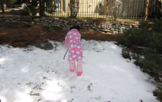 Image of little girl frolicking in the snow in her back yard.